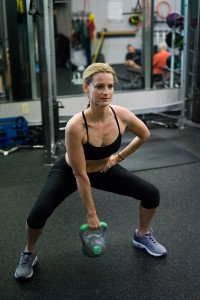 Squat with a wide stance holding kettle bell with an overhand grip. As you rise, lift your elbow toward the ceiling.